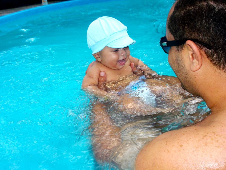 muž s dítětem v bazénu